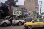 """Qamishli, autonomous Democratic Federation of Northern Syria – Billboards of Bashar al-Assad overlook a traffic circle in downtown Qamishli. A section of the traffic circle is controlled by Assad's regime, while the remainder is held by coalition SDF forces. (Bottom Left) A regime traffic officer standing in the SDF controlled part of traffic circle."""""""